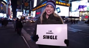 "The Clichè: ""You have to put yourself out there."" The Challenge: Walk around NYC with a sign that says, ""I'm currently SINGLE."""