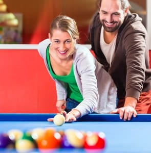 A photo of a couple playing pool