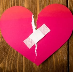 Photo of a ripped paper heart with a Band-Aid over it