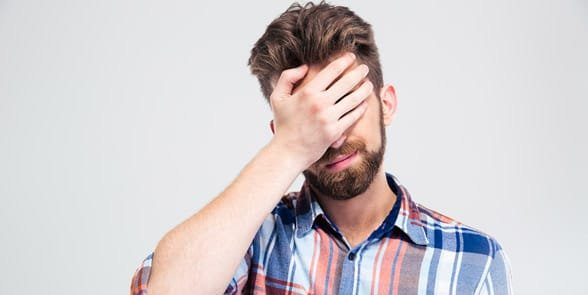 Photo of an embarrassed man covering his face