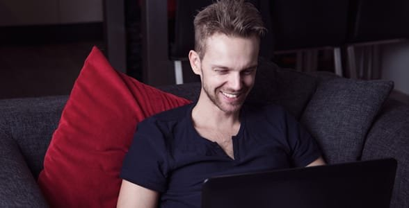 Photo of a guy smiling at a laptop