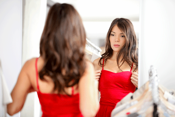 Photo of a woman looking at herself in a mirror