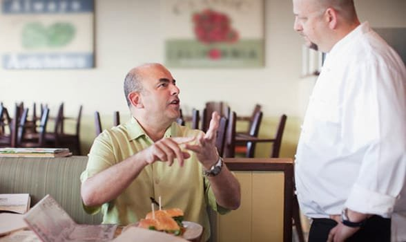 Photo of a man yelling at a waiter