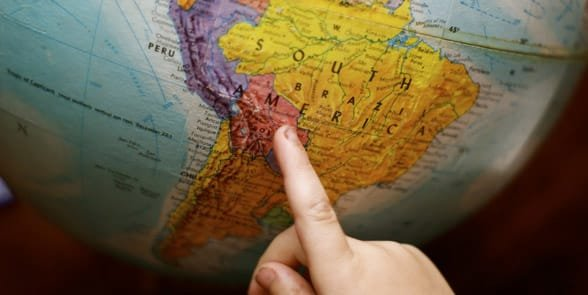 Photo of a person pointing at a globe