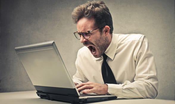 Photo of a man screaming at a computer