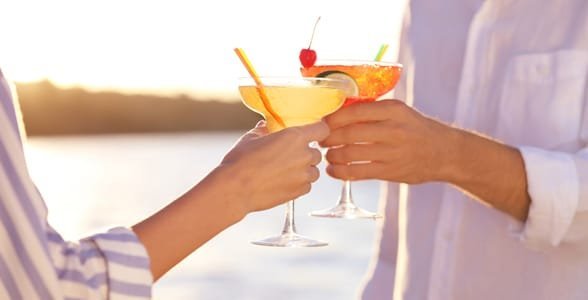 Photo of a couple holding cocktails