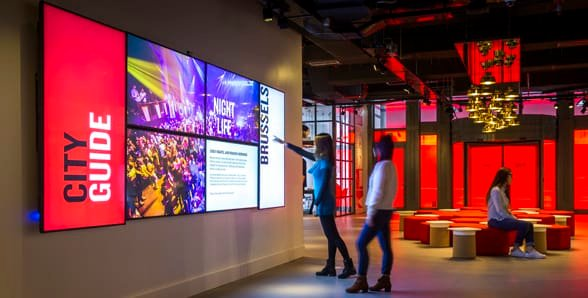 Photo of guests looking at Radisson RED's Digital Wall