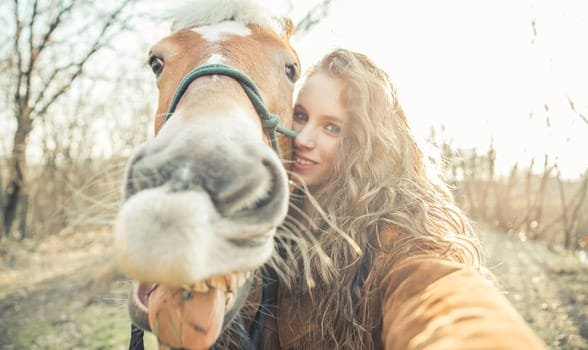 Photo of a woman taking a photo with a horse
