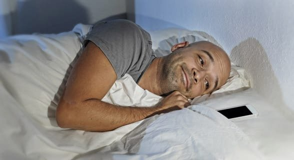 Photo of a man sleeping with his phone