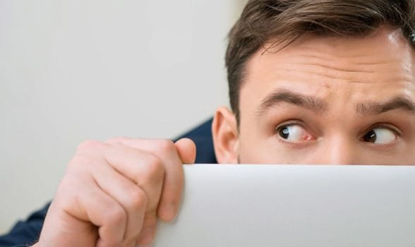 Photo of a man hiding behind a laptop