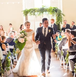 Photo of Berty Mandagie and his wife Emily walking up the aisle