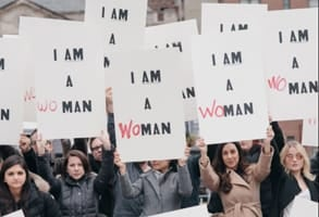Photo of women carrying Interbrand's I AM A WOMAN signs in 2017
