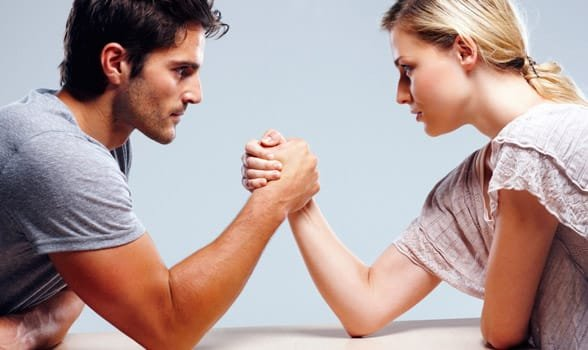 Photo of a man and woman arm wrestling