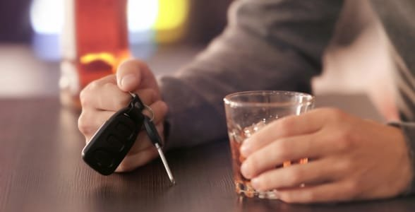 Photo of someone holding a drink and car keys