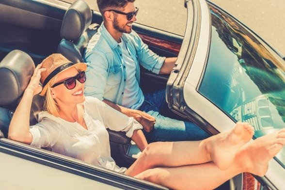 Photo of a couple smiling in a convertable