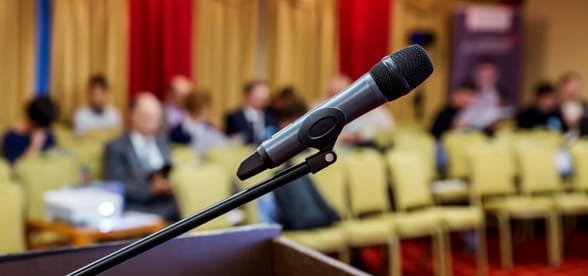 Photo of a microphone on a podium and attendees in a conference hall