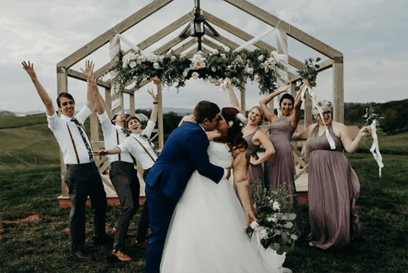 Photo of a wedding party surrounded by floral decor