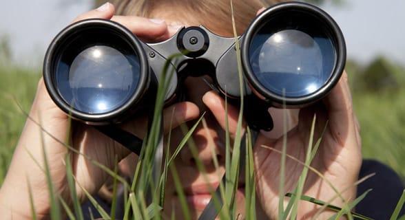 Photo of a woman looking through binoculars