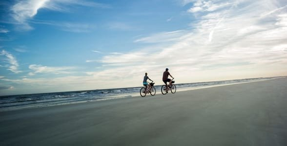 Photo of a couple biking on the beach at Hilton Head Island