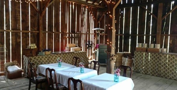 Photo of tables in a barn at the Hummingbird Room