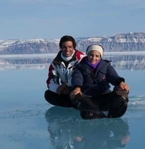 Photo of a couple sitting on the ice during an Arctic Kingdom expedition
