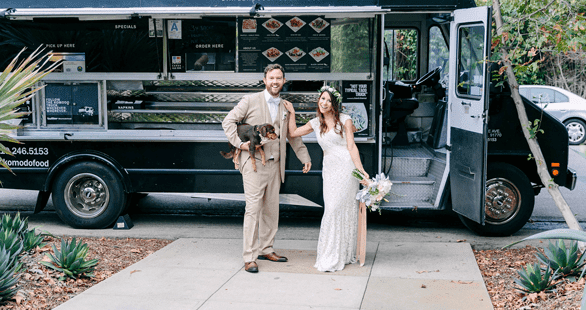 Photo of a bride and groom with a food truck