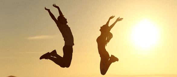 Photo of couple jumping for joy
