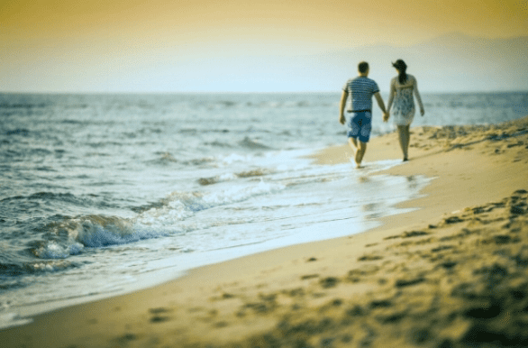 Photo of couple walking on the beach