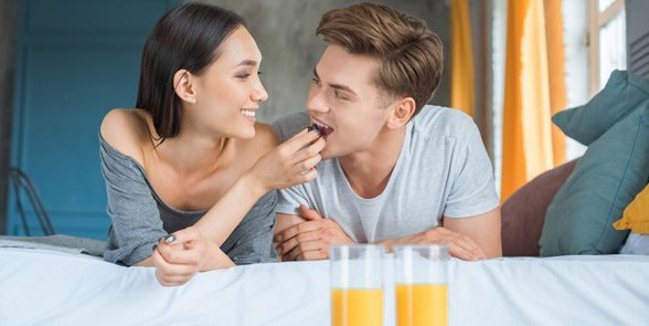 Photo of a couple having breakfast in bed
