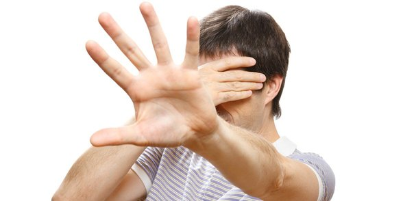 Photo of a man with his hand in front of his face