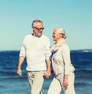 Photo of a senior couple walking on the beach