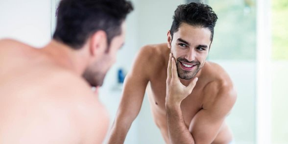 Photo of a man looking at himself in the mirror