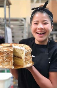 Photo of a Purebread baker with a cake