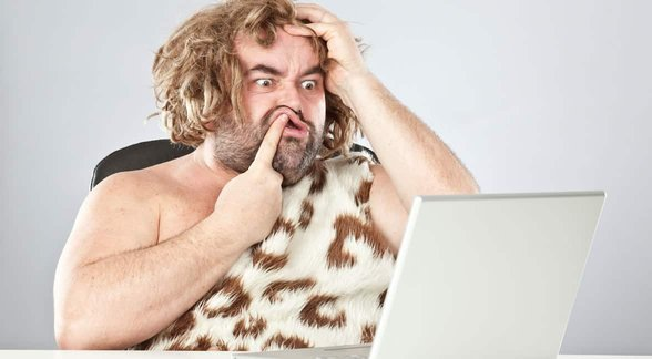 Photo of a caveman on a laptop
