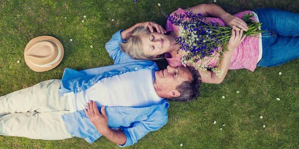 Photo of mature couple laying in the grass