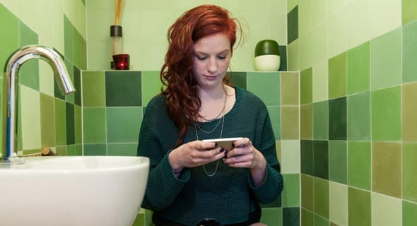 Photo of woman texting while using the restroom