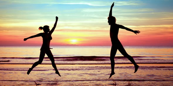 A photo of a couple jumping on the beach