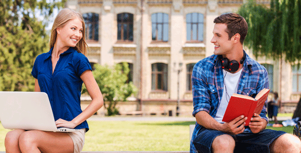 Photo of a man and woman looking at each other on a bench