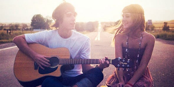 Photo of a boy playing guitar for a girl