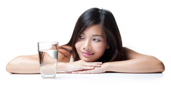 Photo of a woman looking at glass as half full
