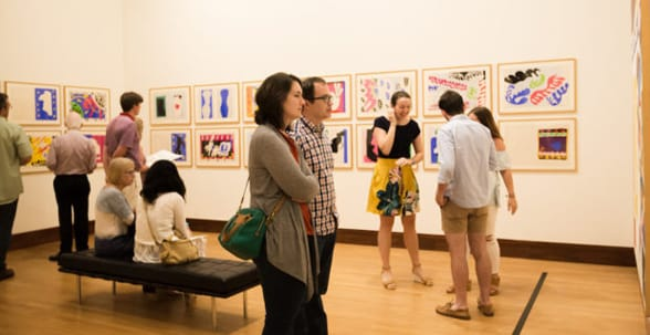 Photo of people mingling at an art exhibition at OKCMOA