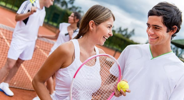 Photo of a man and woman playing tennis