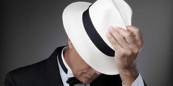 Photo of a man tilting his hat
