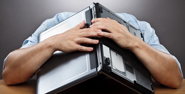 Photo of a guy burying his head under a laptop
