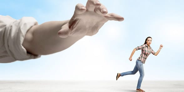 Photo of a woman running away from a man's hand
