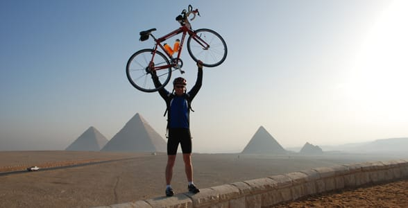 Photo of a man posing with his bicycle above his head