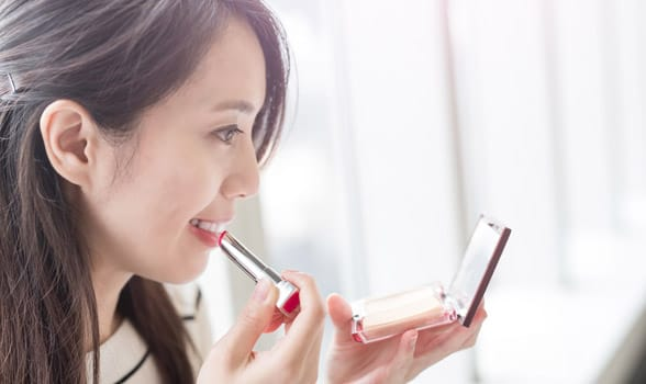 Photo of a woman putting makeup on