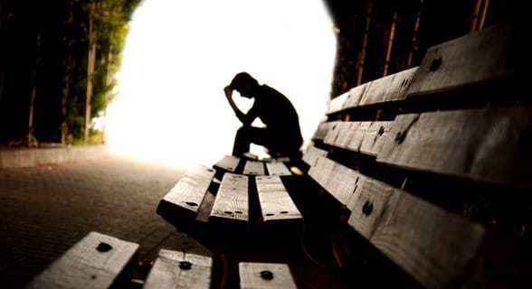 Photo of a sad man thinking on a bench
