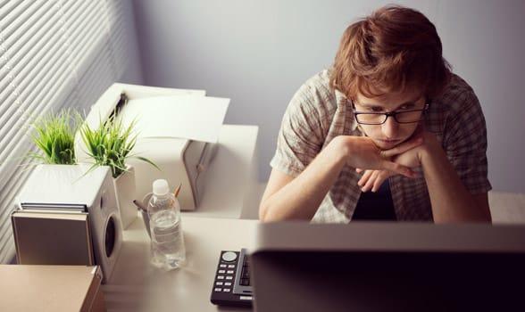 Photo of a man staring at his computer