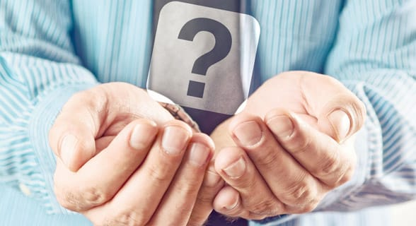 Photo of a man holding a question mark